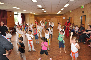 kids in martial arts class putting their hands up to answer a question